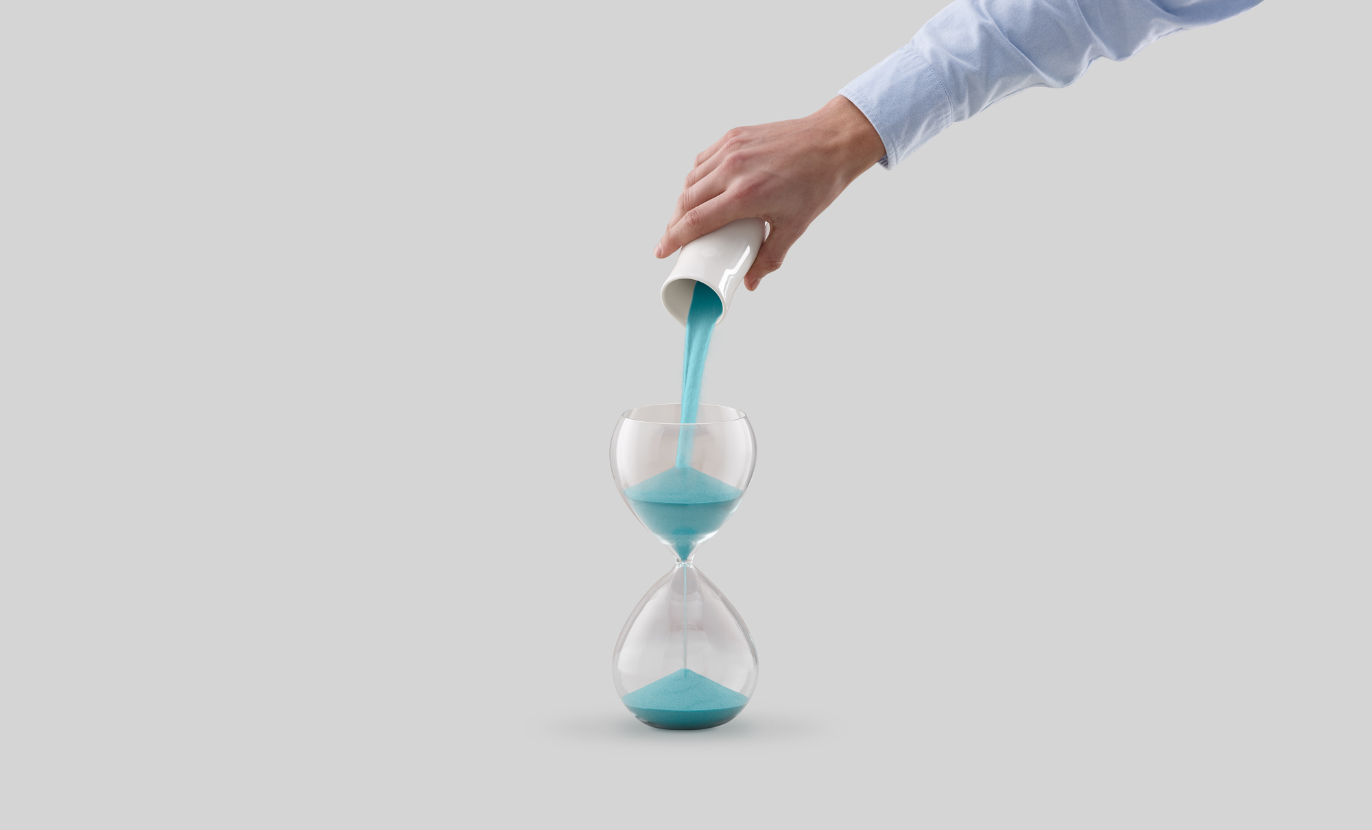 A hand pouring more sand into the top of an hourglass